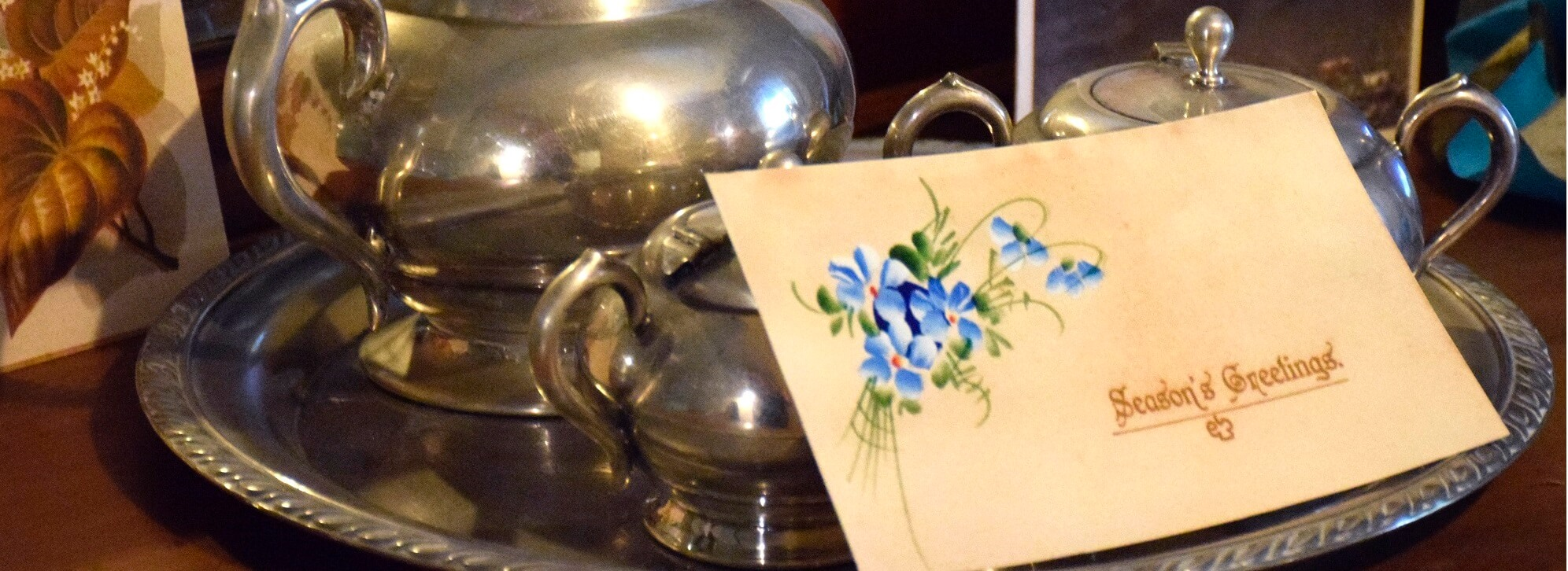 cropped image of silver teapot with old card leaning against it with the words 'Seasons Greetings' and a blue flower in the corner. Part of the Christmas at the Old Treasury Building 2018 display