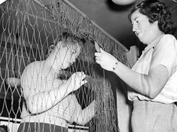 Shows two women making camouflage nets. They were members of General Motors Holden's staff and were voluntarily making the nets.