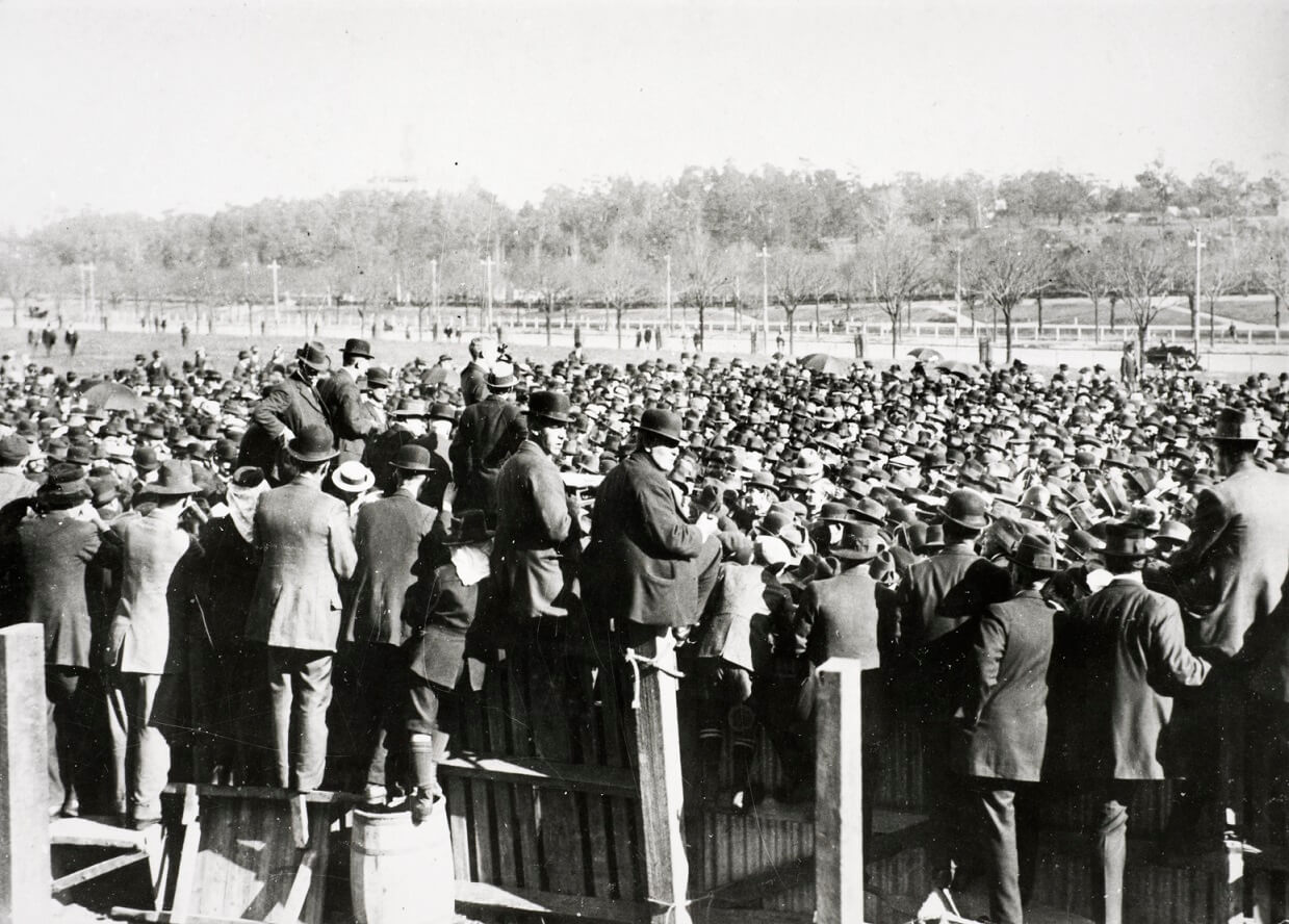 black and white image showing a crowd of people (appears to all be men) wearing bowler hats all stand shoulder to shoulder facing a man standing slightly above them. In the foreground men climb and stand upon a timber and corrugated iron fence facing away from the camera.